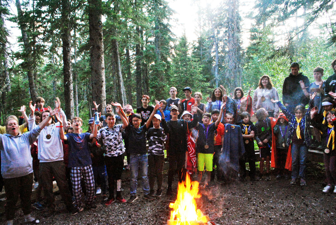 Campers and staff share stories around the campfire at Camp Impeesa's outdoor summer camps.